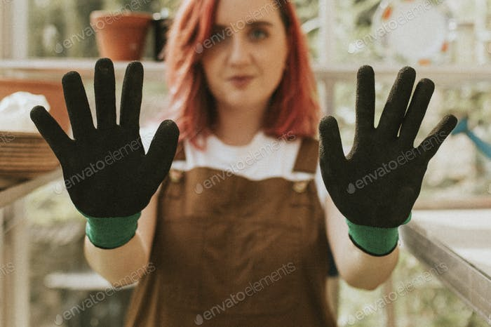 Young woman gardener with black gloves in small organic farm