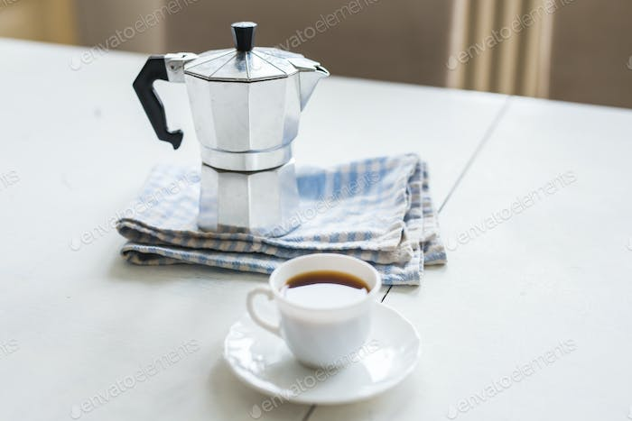 Vintage coffee pot, a cup of coffee is on a white table