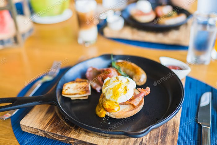 Breakfast set with egg benedict sausage in hot pan