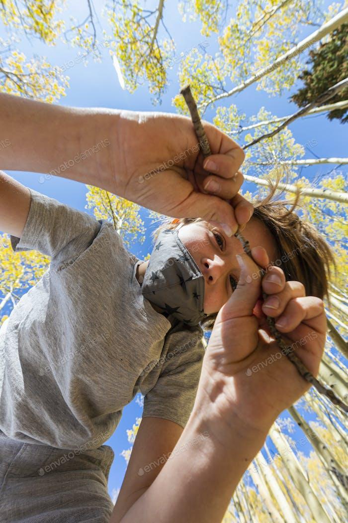 schaut auf Junge mit COVID-Maske mit Herbsteseln oben