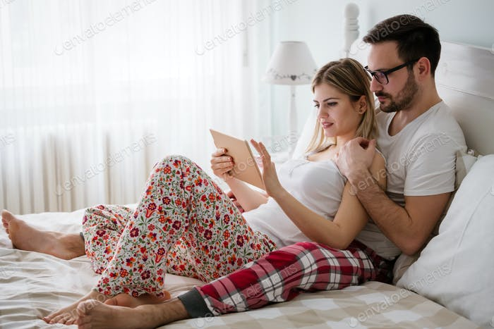 Happy couple in love using tablet in pajamas