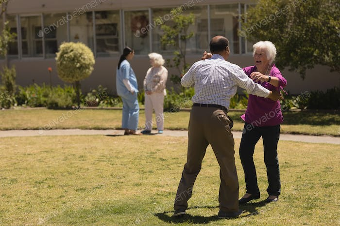 Front view of happy senior couple dancing and laughing together in garden on sunny day