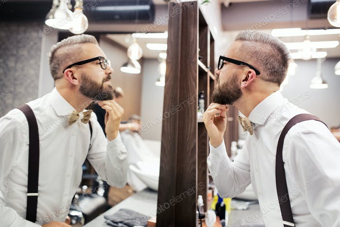 Hipster man client with glasses looking in the mirror in barber shop.
