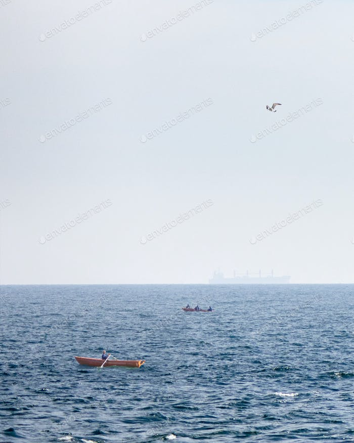 View of fishing boats on a background of blue open sea and a tanker blurred on the horizon