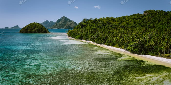 Aerial panoramic view of Las Cabanas sandy beach with coconut palm trees in El Nido, Palawan