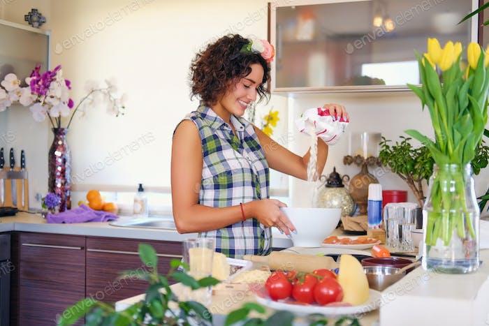Положительная брюнетка женщина делает тесто на кухне.