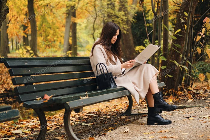 Side view of attractive brunette girl intently reading newspaper sitting on bench in park