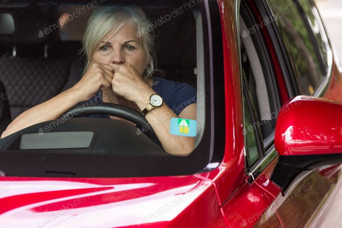 Scared elderly woman looks with horror through the window of a red car