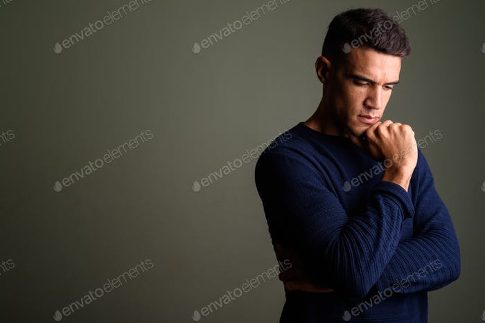 Young handsome man thinking against colored background