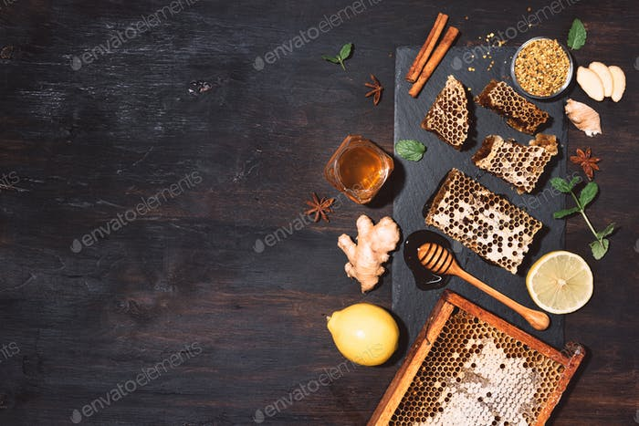 Ingredients for healthy hot drink. Lemon, ginger, mint, honey, apple and spices on black slate tray