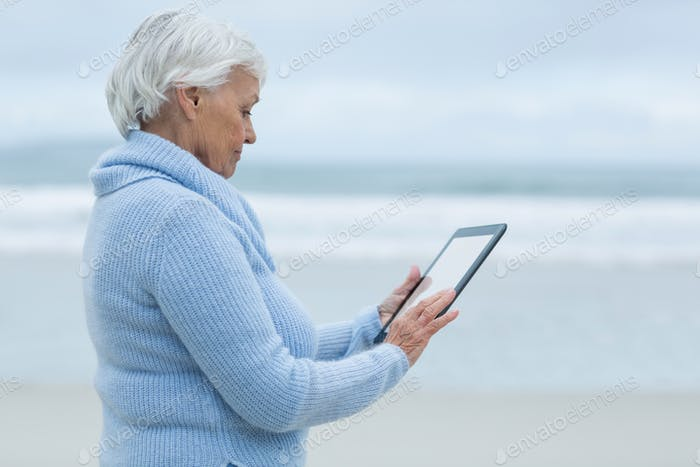 Senior woman using digital table on the beach