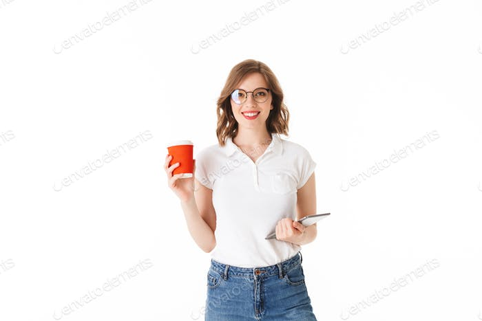 Young beautiful lady in eyeglasses standing with cup of coffee to go and the tablet in hands