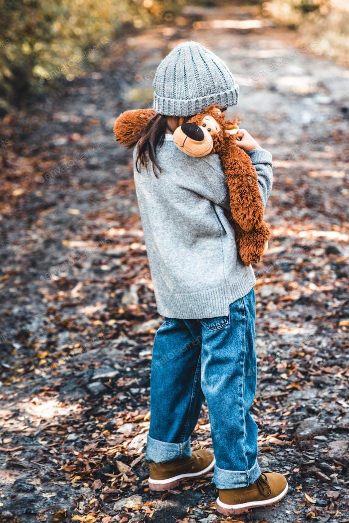 Kleines Mädchen umarmt ihren Bär auf einem Hintergrund der Natur, Herbst, Durba