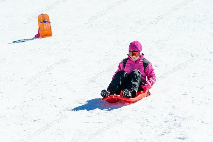 Little girl sledding at Sierra Nevada ski resort