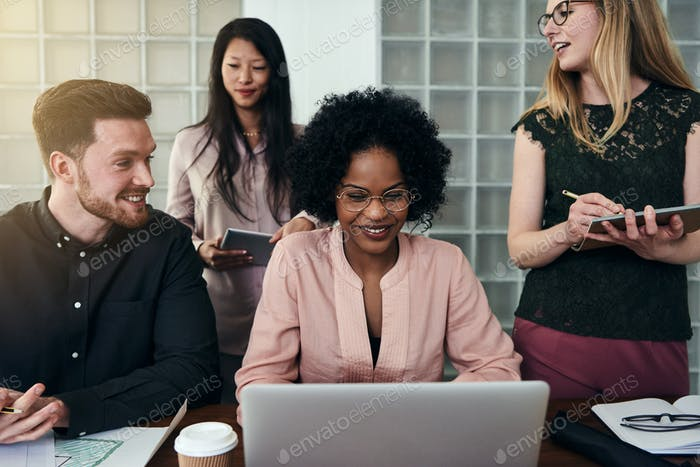 Smiling colleagues working on a laptop together in an office