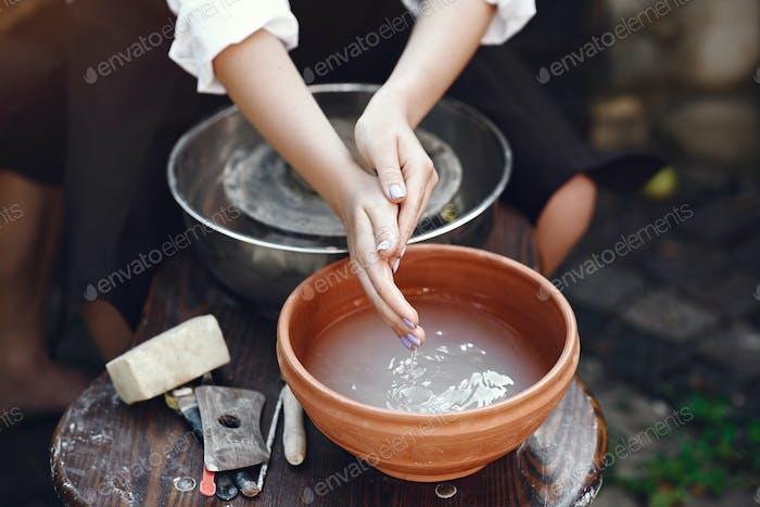Gente haciendo un vaze de una arcilla en una máquina de cerámica