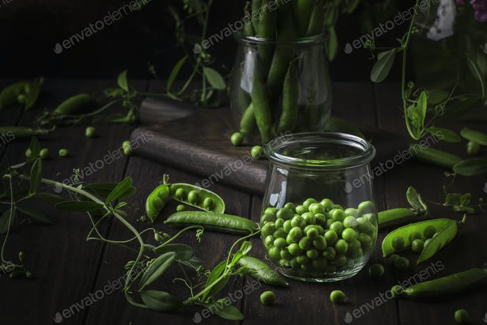 Peeled fresh sweet green peas in glass jar