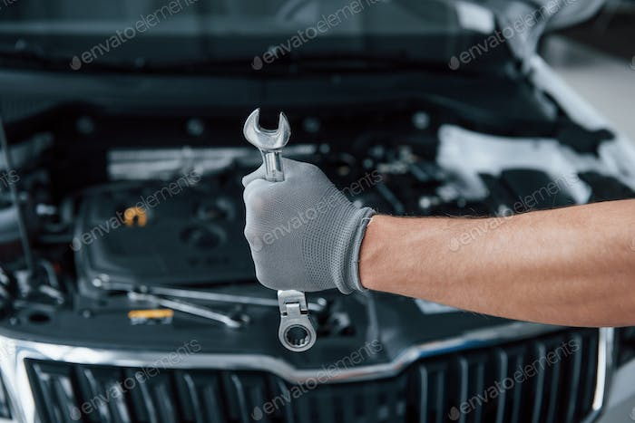 Protective gloves. Man's hand holds wrench in front of broken automobile