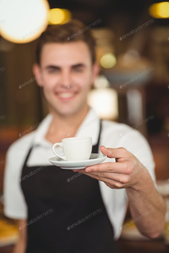 Smiling barista offering cup of coffee to camera at coffee shop