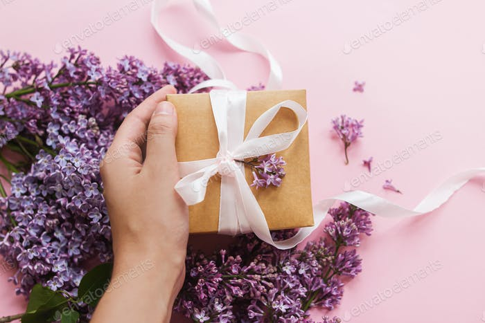 Happy mothers day and valentine's day. Hand holding gift box with ribbon and lilac flowers on pink
