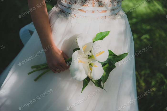 Young beautiful bride holding a bouquet.