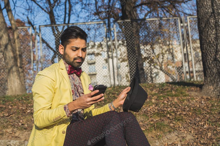 Indian handsome man texting in an urban context
