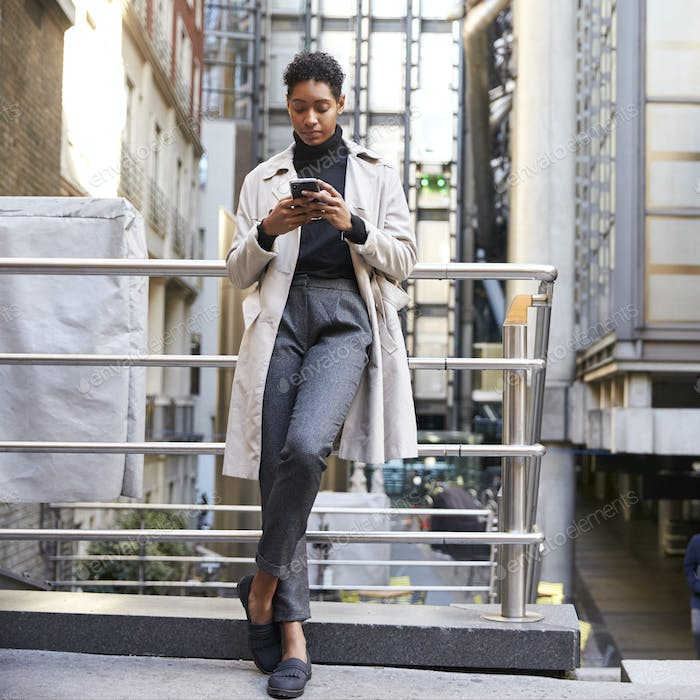 Fashionable young black woman using her smartphone, full length, low angle