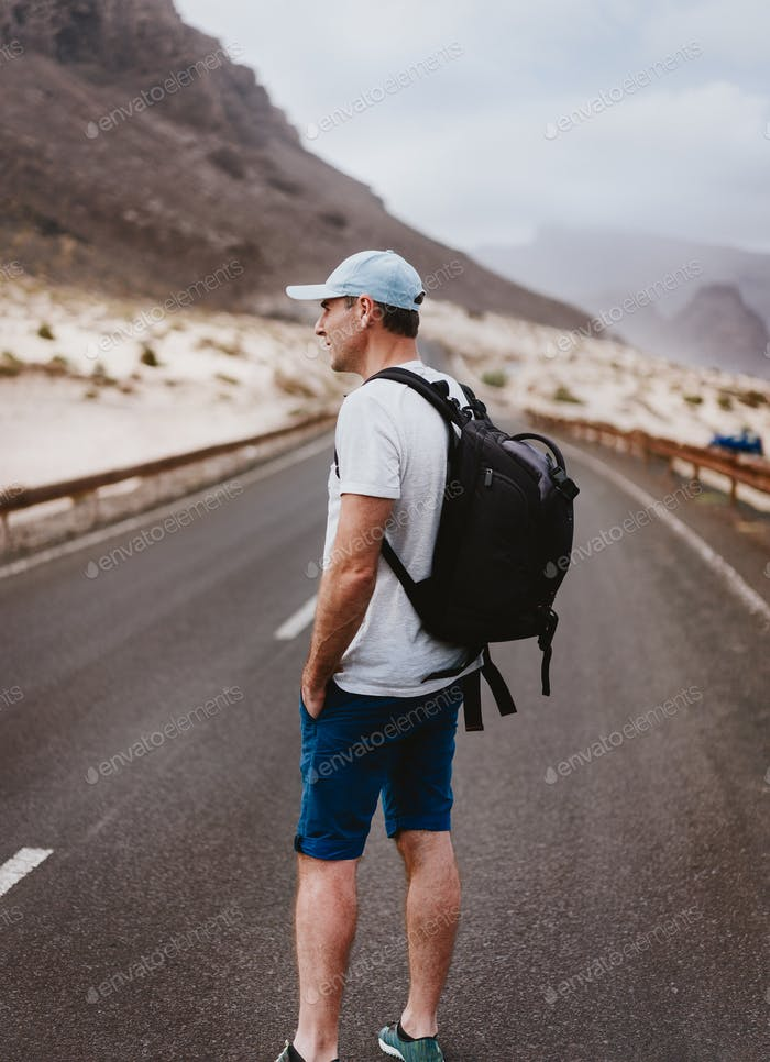 Sao Vicente Cape Verde. Traveler with backpack standing in the center of asphalt road. Huge volcanic