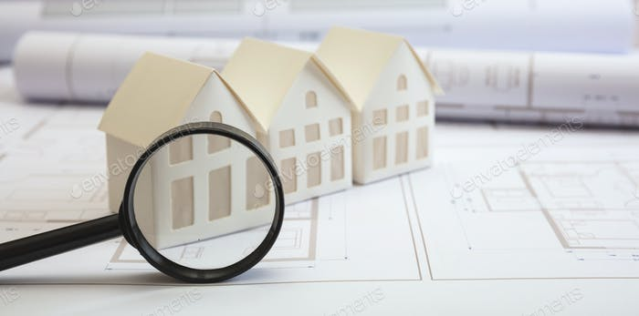 Construction concept. Residential building drawings and architectural house models on an office desk
