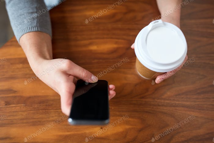 close up of woman with smartphone and coffee