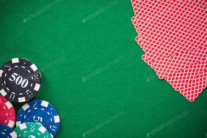 Casino chips and poker cards on green felt, background