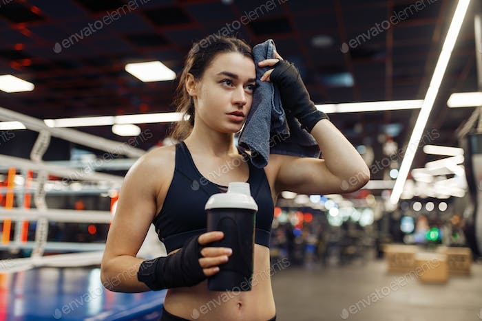Tired woman wipes her sweat after boxing training