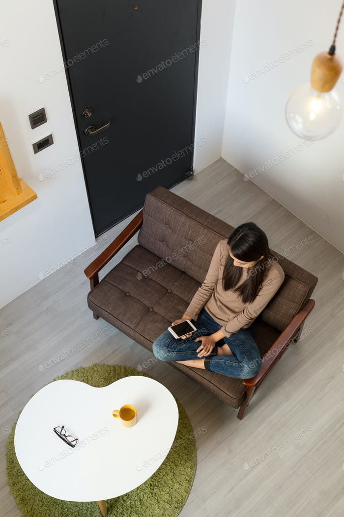 Top view of woman use of the cellphone at living room