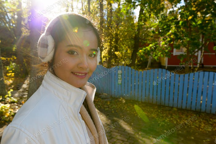 Portrait of happy young beautiful Asian woman smiling in the forest