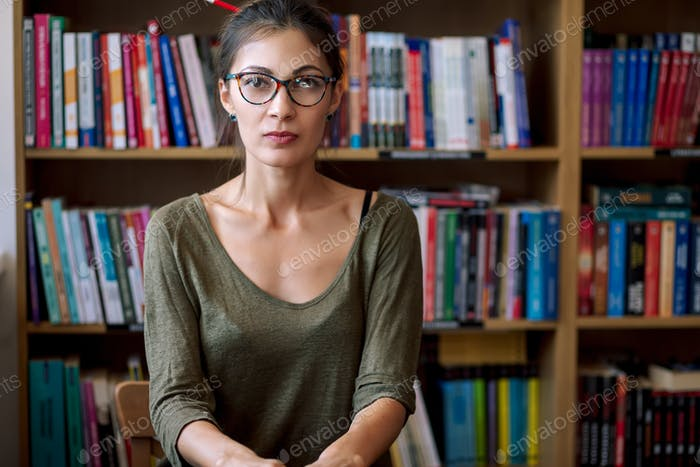Portrait of beautiful young woman in the bookstore