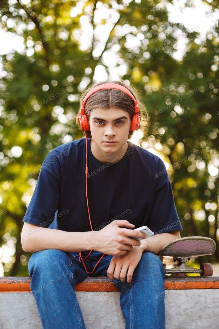 Young guy in orange headphones holding cellphone in hand thought