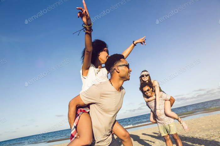 Two young men giving their girlfriends piggyback rides