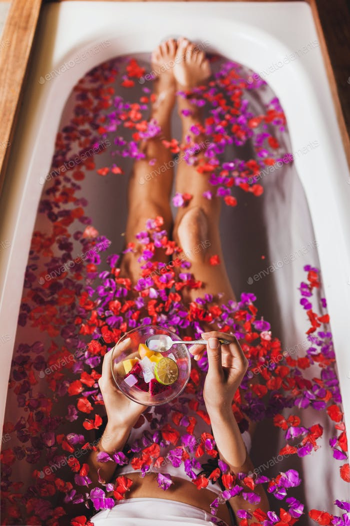 Woman legs in flower bath in spa. Hands holding plate with fresh fruit salad, view from above