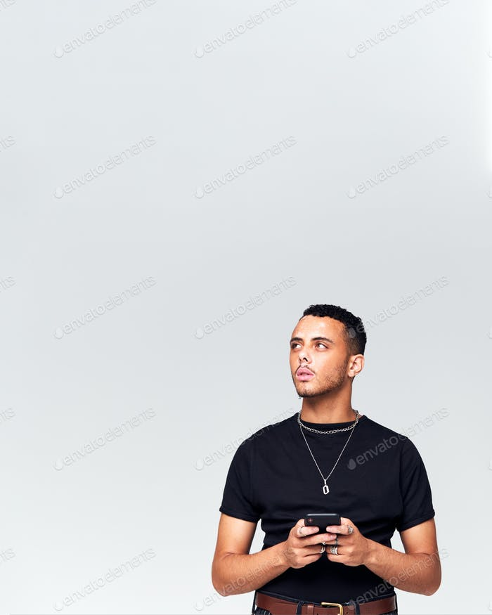 Studio Schuss von Kausally gekleidet jungen Mann mit Handy Blick aus Kamera