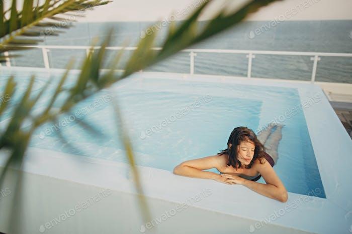 Beautiful young woman relaxing in pool, enjoying warm sunlight and wind
