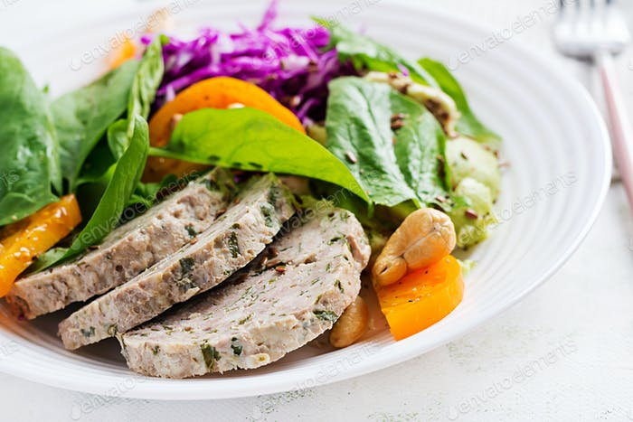 Buddha bowl dish with meatloaf, chicken meat, avocado, cabbage and nuts.