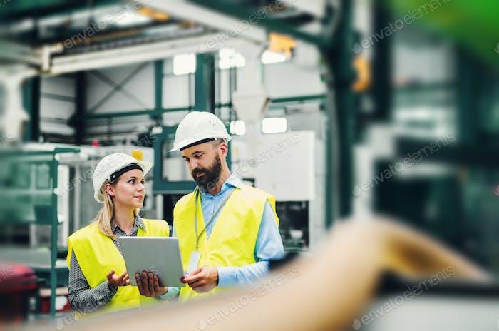 Ein Porträt eines Industriemannes und einer Ingenieurin mit Tablette in einer Fabrik.