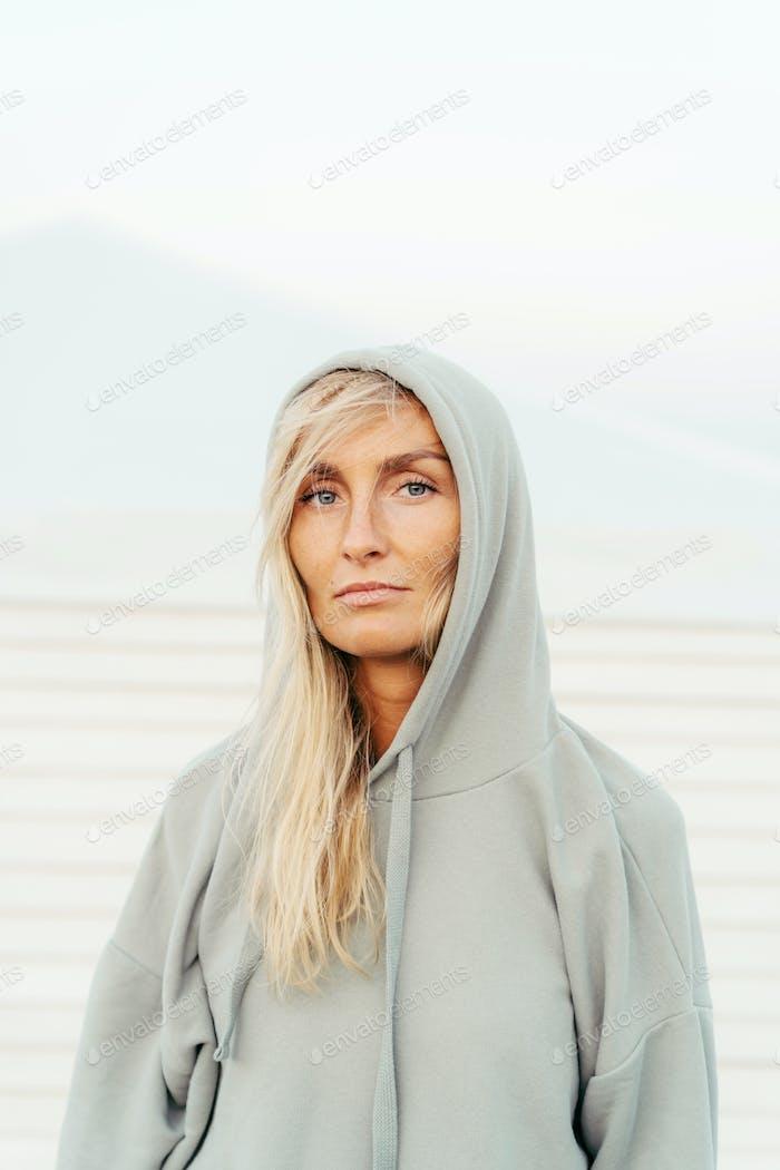 Mujer rubia bronceada blanca de treinta años fuera en una sudadera gris.