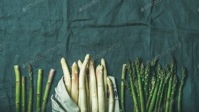 Fresh green and white asparagus in towel over grey table