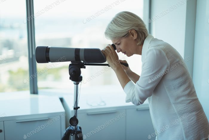 Side view of businesswoman using telescope