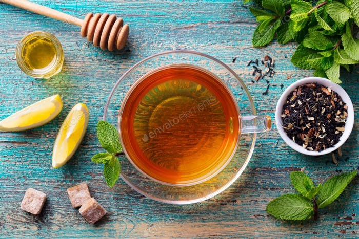 Tea Cup with Mint Leaf and Honey. Wooden Background. Top View.