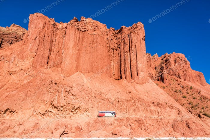 Bus and Dramatic Red Cliffs in Bolivia