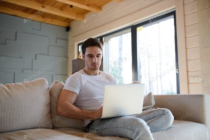Man on sofa using gadget