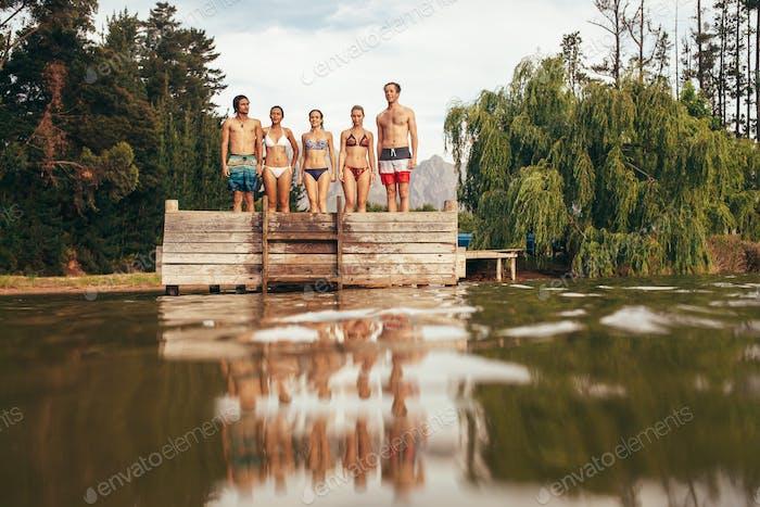Junge Freunde stehen auf Steg am See