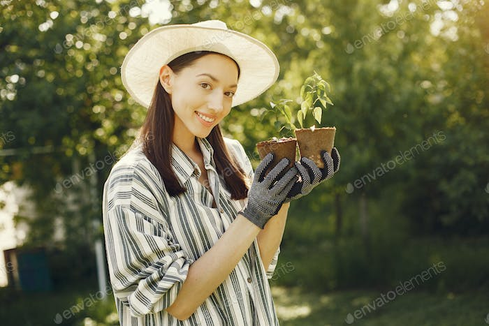 Woman in a hat holding flowerpots